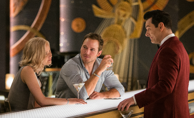 Aurora (Jennifer Lawrence) and Jim (Chris Pratt) pay Arthur (Michael Sheen) a visit at the Grand Concourse Bar in Columbia Pictures' Passengers. ©2016 CTMG, Inc. All Right Reserved.