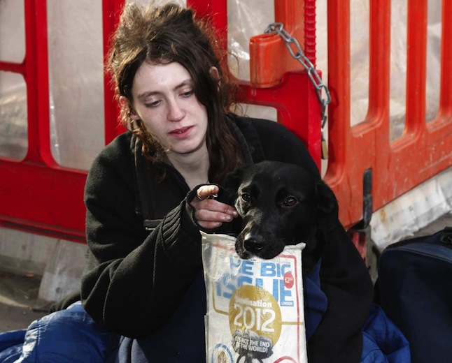 England, London, Big Issue seller with her dog.