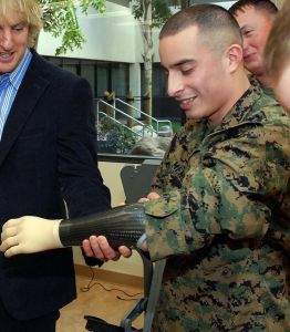 Owen Wilson holding the myoelectric arm of a marine. The prosthesis control the limbs by converting muscle  movements to electrical signals picked up by electrodes. Credit@GregMitchellViaWikimediaCommons